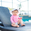 Cute infant girl with a white hat and a Light Pink Long Sleeve Rashguard Shirt sitting by a pool in a lawn chair.