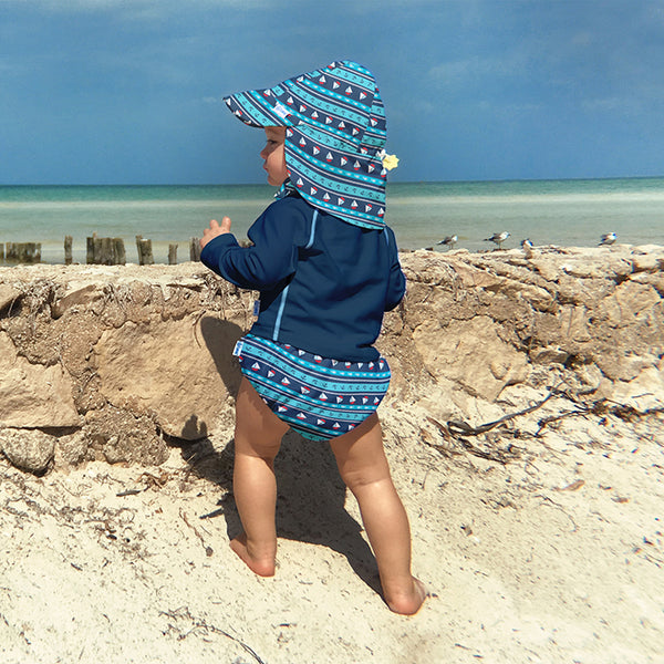 young baby standing on the beach looking a the waves while wearing a Navy Long Sleeve Rashguard Shirt