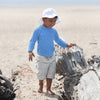 Young boy with a Light Blue Long Sleeve Rashguard Shirt inspecting the rocks on the beach