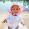A pretty little baby girl with a Brim Sun Protection Hat on looking up into the camera.