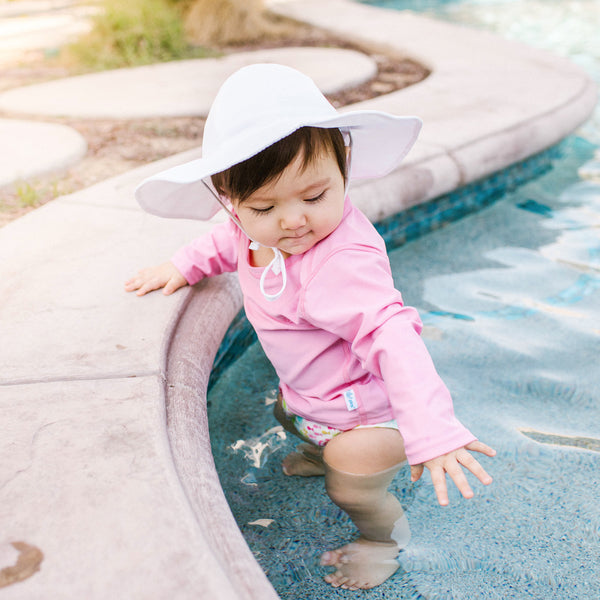 A cute young toddler girl standing in a shallow pool reaching for the water below her while wearing a white brim hat and a Pink Easy-on Rashguard Shirt.