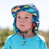 A close up of the face of a little boy looking into the distance while wearing a Flap Hat and an Aqua Easy-on Rashguard Shirt.