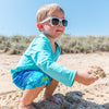 A cute little dude squatting on the beach and picking up sand with a seashell like a tortia chip and queso. He rocking some white Flexible Sunglasses and aqua swim outfit.