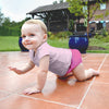 A smiling young toddler girl crawling across tiled ground in the backyard while wearing a Light Pink Pinstripe Cap Sleeve Rashguard Shirt and pink swim diaper.