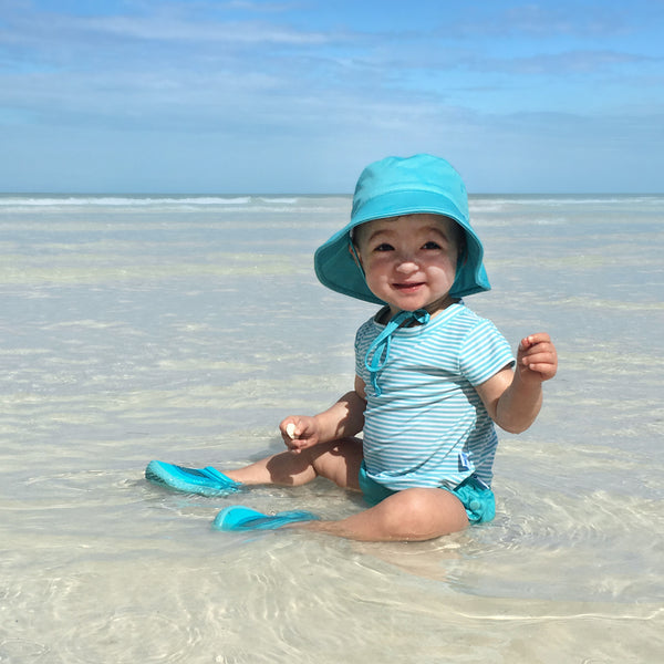 A little girl sitting in the shallow water on the beach while wearing a light aqua pinstripe Cap Sleeve Rashguard Shirt