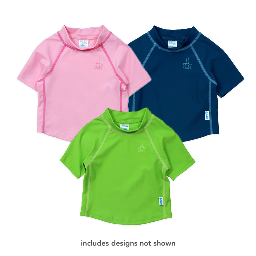 "Three different short sleeve rashguards that are light pink, green, and navy colors. At the bottom is says ""includes designs not shown""."