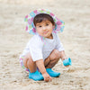 A cute young girl wearing Brim Sun Protection Hat while squatting and playing in the sand. She is looking at the viewer with a questionable smirk.