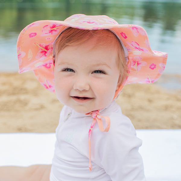 An adorable baby girl wearing the coral hibiscus Brim Sun Protection Hat while smiling up at the viewer.