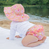 A little girl with coral hibiscus Brim Sun Protection Hat and matching swim diaper about to take off crawling through the sand.