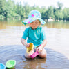 A little blonde girl kneeling in the shallow lake with an aqua coral reef Brim Sun Protection Hat while playing with toy boats.
