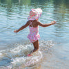 A cute young girl skipping away into the water towards the camera while wearing the light pink dragonfly floral Brim Sun Protection Hat and a matching swimsuit.