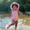 A cute young girl skipping through the water towards the camera while wearing the light pink dragonfly floral Brim Sun Protection Hat and a matching swimsuit. She has a funny cheesy smile going on.