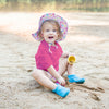 A blonde curly haired girl wearing a pink sealife Brim Sun Protection Hat is playfully screaming while digging in the sand with toy cups.