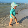 A young toddler walking along the shore with her light Aqua Sea Friends Flap Sun Protection Hat and a swimming outfit to match.