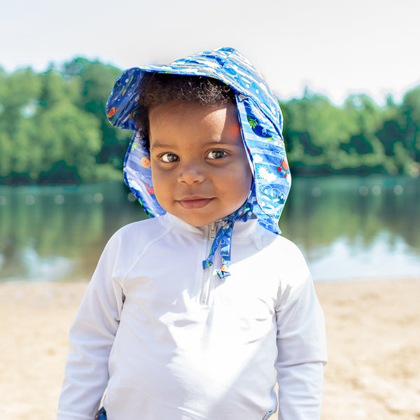 A young boy looking intently at the viewer with a little smile and his Royal Blue Sea Friends Flap Sun Protection Hat on.