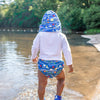 A little boy walking away along the lake shower and wearing his Royal Blue Sea Friends Flap Sun Protection Hat and swim diapers to match.