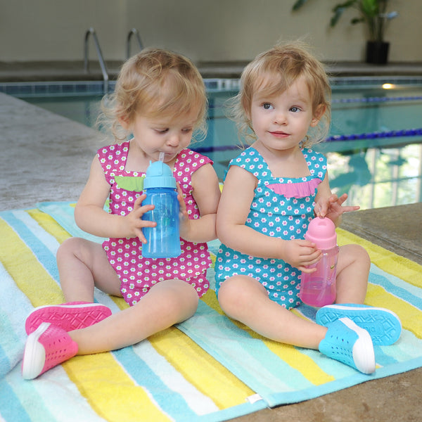 Two little toddler girls sitting pool side while sipping out of their straw bottles. The girl on the left is wearing the pink Classic Ruffle Swimsuit Top and the other is wearing the blue swimsuit.