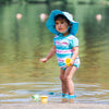 A young girl standing in a lake with toy cups around her while wearing the aqua stripe Classic Bow Swimsuit Bottom w/Built-in Reusable Absorbent Swim Diaper and rashguard to match.