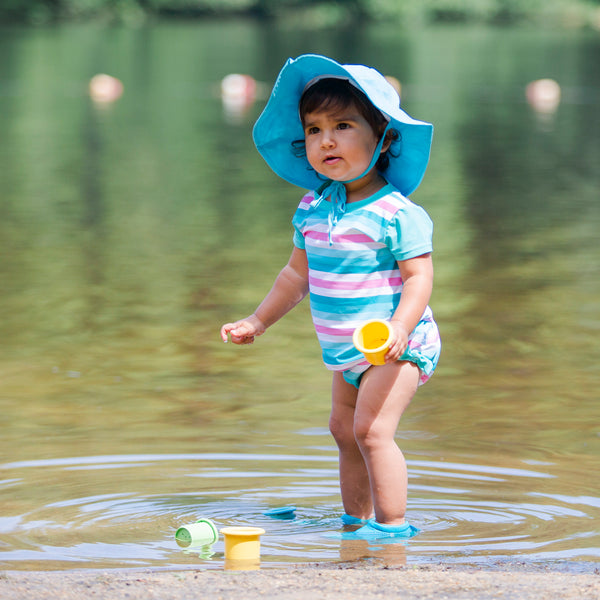 A young girl standing in a lake with toy cups around her while wearing the aqua stripe Classic Two-piece Cap Sleeve Rashguard Set with Built-in Reusable Absorbent Swim Diaper.