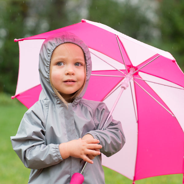 A young girl with the gray Lightweight Raincoat and an umbrella standing outside
