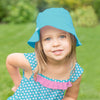 A sweet young girl fashioning the aqua daisy Classic Ruffle Swimsuit Top and an aqua bucket hat with her hand on her hip.