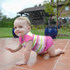 A smiling young toddler girl crawling across tiled ground in the backyard while wearing a Rashguard Shirt and pink swim diaper.