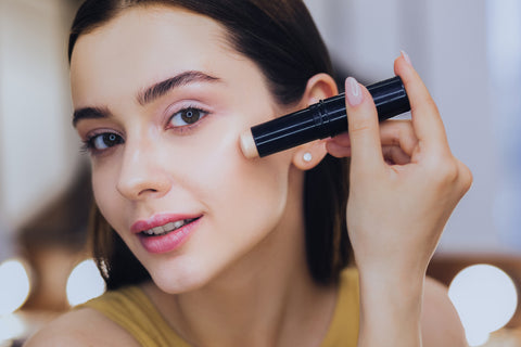 Charming beautiful woman using concealer stick