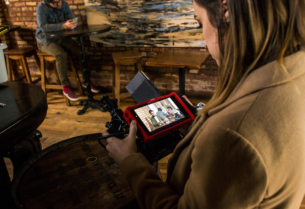 Woman holding Atomos Flame Ninja connected to a Teradek Bolt receiver