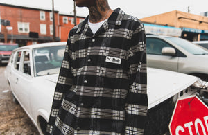 Man standing wearing Puma plaid jacket
