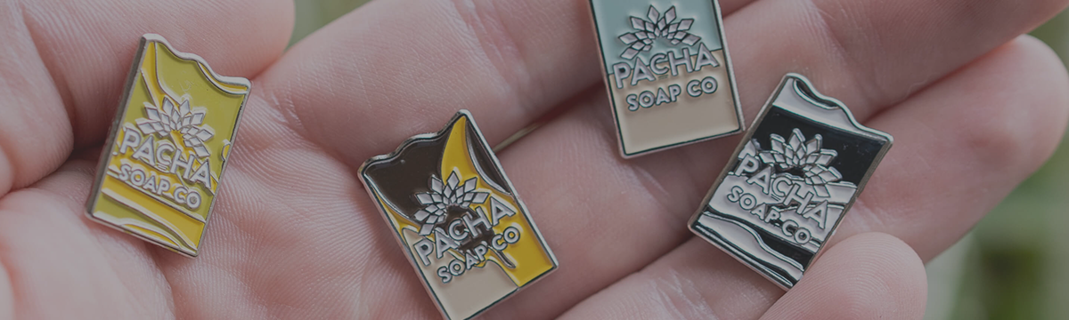 Pacha Soap Enamel Pin Collection displayed on hand