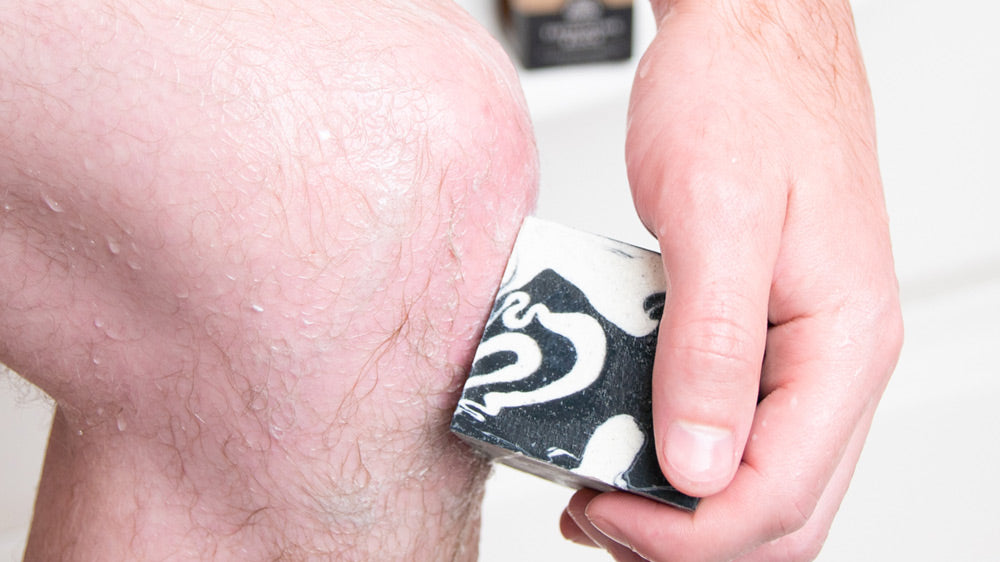 Scrubbing Knee with Clarifying Charcoal Scrub + Suds Exfoliating Block in the Shower