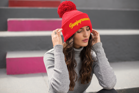 Woman sitting on steps wearing red ganjapreneur pom beanie