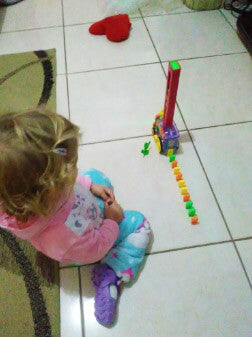 girl playing with dominoes train toy