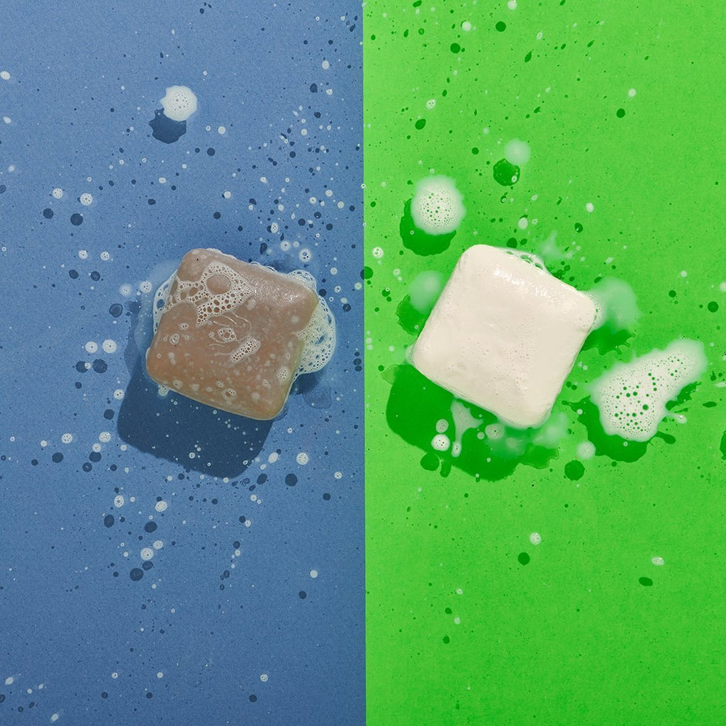 Lathered Juju Exfoliating and Pekee Cleansing Bars on Blue and Green Background