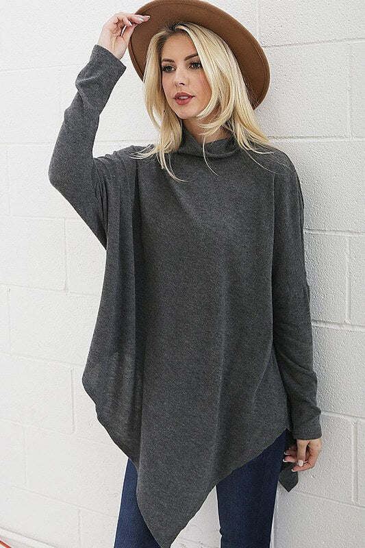 Fun asymmetrical poncho top, great with both jeans and leggings! Pair with you favorite hat or scarf and be street stylish.  Asymmetrical poncho top. Colors available charcoal gray or light gray.  60% Polyester/ 35% Rayon/ 5% Spandex. Priced at $35.00.