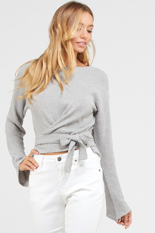 Versatile sweater top that you can pair with jeans, dress pants, or skirts. Light gray sweater with tie wrap belt at the waist and rounded neckline.  Priced at $45.00.