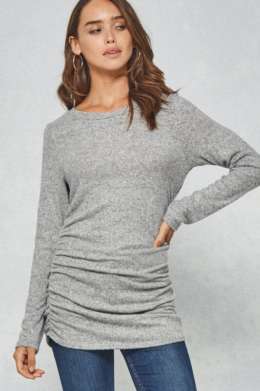 Super soft heather gray brushed knit top featuring round neckline, long sleeves, rouched sides, and fitted silhouette.  21% Polyester 75% Rayon 4% Spandex. Priced at $39.00.