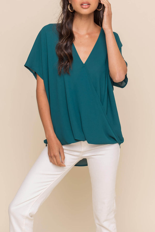 Surplice twist top 100% Polyester, loose fit,  and crossover twist front.  Available in teal and blush.  Priced at $30.00.