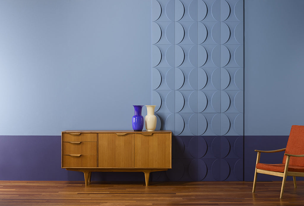 A wall painted to shades of blue with 3D wall panels