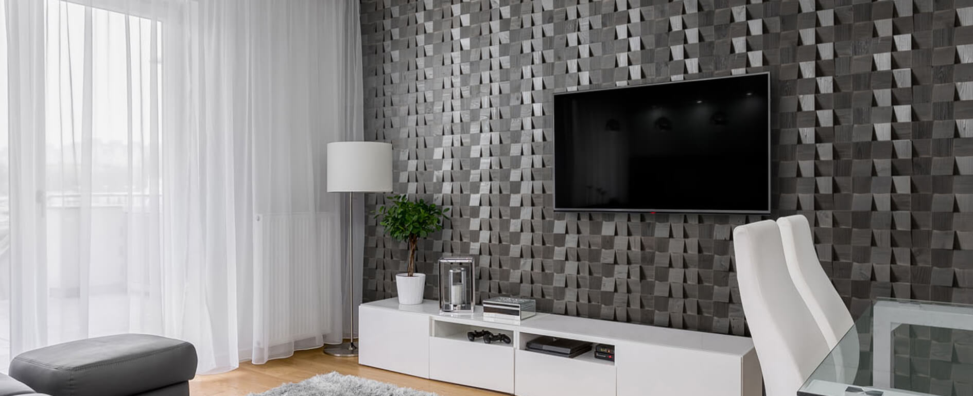 A living room featuring grey 3D wooden wall cladding behind a wall mounted TV