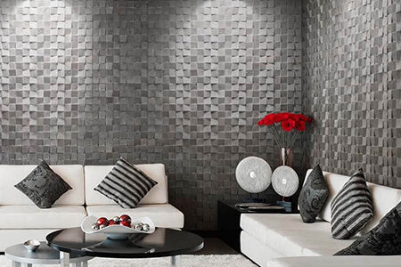 A contemporary living space with grey 3D wooden wall cladding on both walls. The room is styled with white sofas and highlights of red flowers.