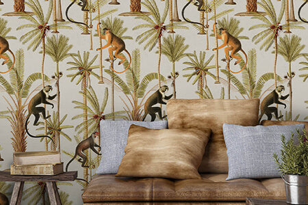 A brown sofa in front of Mind The Gap wallpaper which features monkeys and palm trees on a light background