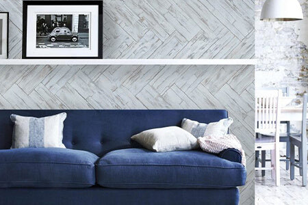 Peel and stick wood wall panels in a whitewash finish are applied to a wall behind a stylish blue sofa