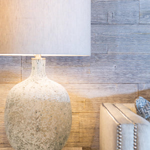 Easily applied wood wall panelling in a living room. The wood grain highlighted by a table lamp
