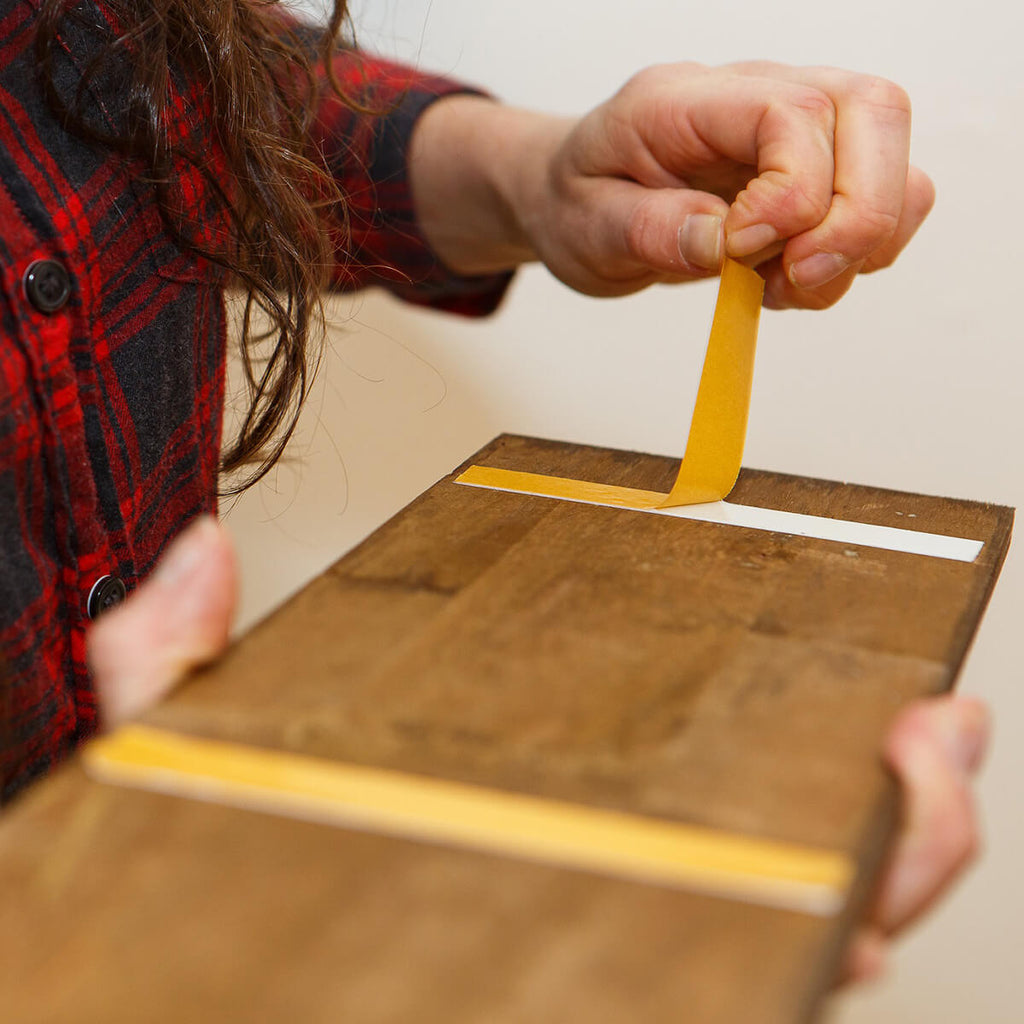 Demonstrating peel and stick application of wood panel