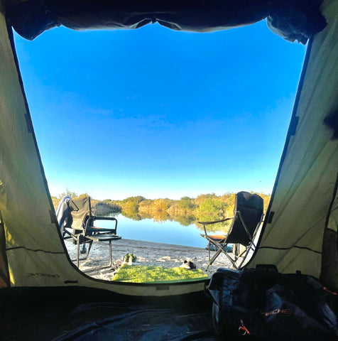 View from inside a tent, looking out on two chairs by a pond.