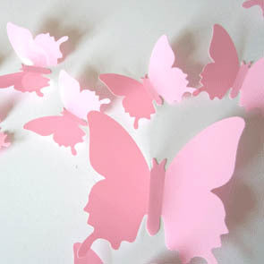 pink plastic 3D decal butterflies in a variety of sizes attached to a wall