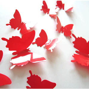 red plastic 3D decal butterflies in a variety of sizes attached to a wall