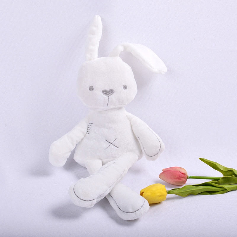 "White stuffed baby bunny plush with grey sewn eyes, nose, ""x"" shaped bellybutton, and mouth on a white background."