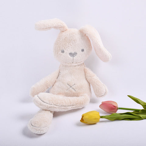 "light beige stuffed baby bunny plush with grey sewn eyes, nose, ""x"" shaped bellybutton, and mouth on a white background."